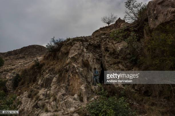 A member of the Afghan Local Police walks out of a cave where allegedly members of ISISK stored weapons near the area where the United States dropped...