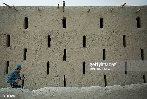 A member of the Afghan National Police tries to make a call on his cell phone as he stands outside an enclosed vineyard at a settlement near the...