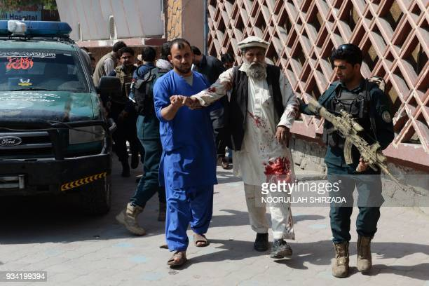 A member of the Afghan security forces and a medic staff assist an injured man walk to a hospital following a bomb blast in Jalalabad on March 19...