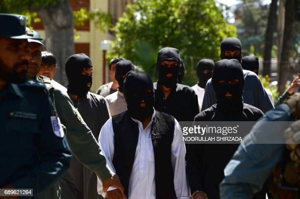 A member of the Afghan security forces escorts alleged Islamic State fighters being presented to the media at the police headquarters in Jalalabad on...