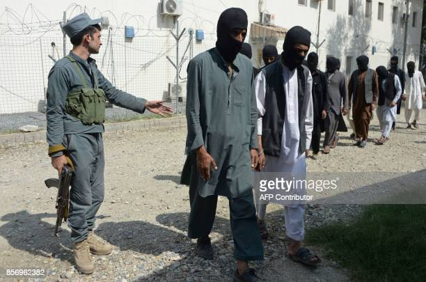 A member of the Afghan security forces escorts alleged Islamic State fighters and Taliban being presented to the media at the police headquarters in...