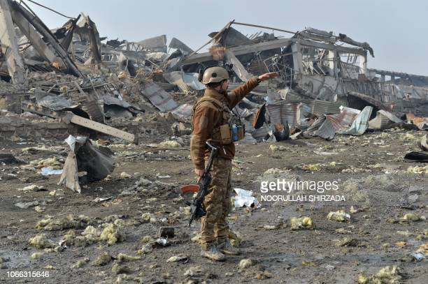 A member of the Afghan security forces gestures at the site of a suicide bomb attack outside a British security firm's compound in Kabul a day after...