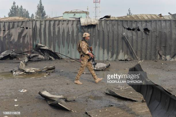 A member of the Afghan security forces walks at the site of a suicide bomb attack outside a British security firm's compound in Kabul a day after the...