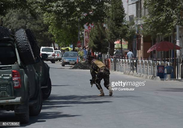 A member of the Afghan security forces walks on the street at the site of a suicide blast near Iraq's embassy in Kabul on July 31 2017 A series of...