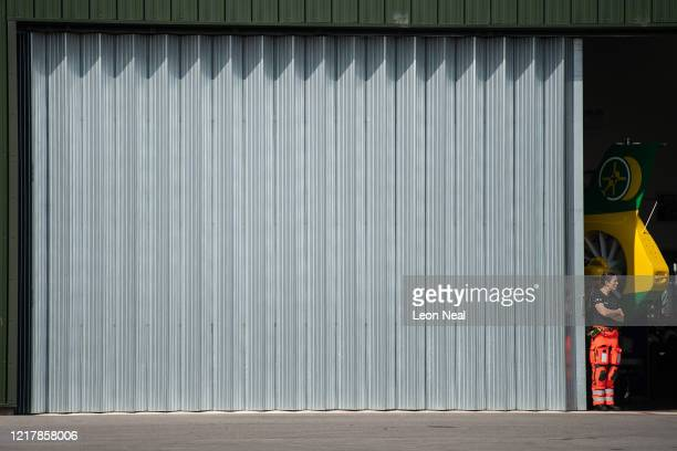 A member of the Air Ambulance Service looks on from a hangar at Thruxton Aerodrome as members of the UK Armed Forces work with NHS medical staff and...