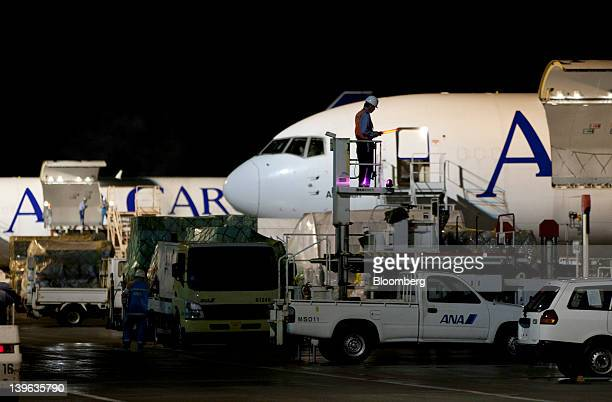 A member of the airport ground staff waits for the arrival of an All Nippon Airways Co cargo aircraft at the company's cargo hub terminal at Naha...