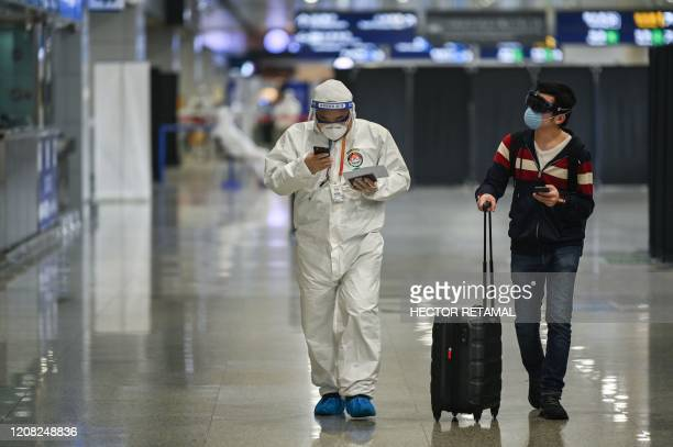 A member of the airport security wearing protective gear as a preventive measure against the COVID19 coronavirus outbreak walks with a passenger upon...
