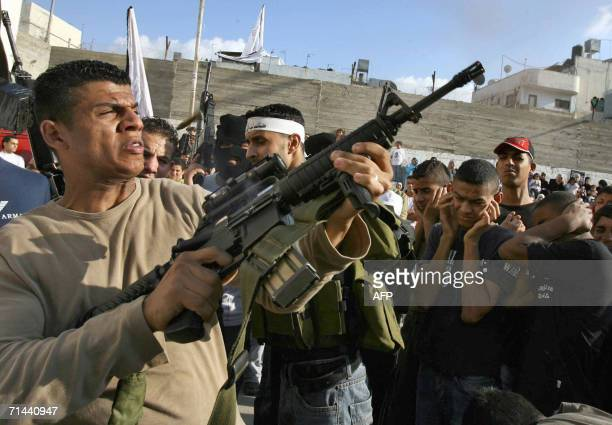 Member of the al-Aqsa Martyrs' Brigades fires into the air as Palestinians rally in the Balata refugee camp in the West Bank city of Nablus 14 July...