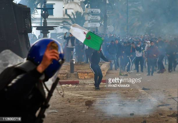 A member of the Algerian security forces holds a rock in his hand as riot forces repsond to protesters gathering in the capital Algiers on March 1...