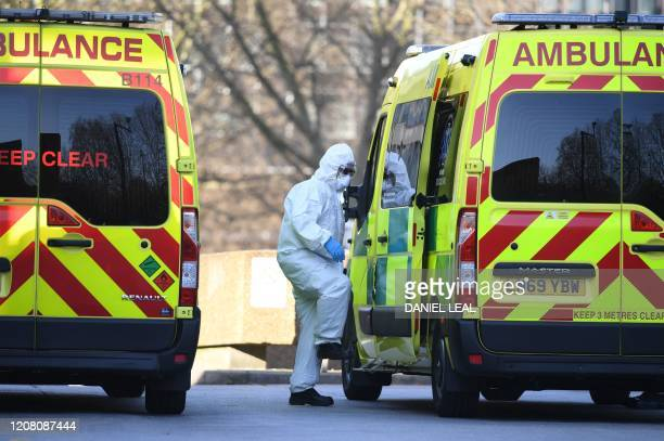 A member of the ambulance service wearing personal protective equipment is seen leading a patient into an ambulance at St Thomas' Hospital in London...