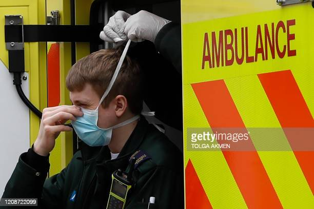 A member of the ambulance services receives assistance from a colleague in tying on a face mask as he stands in an ambulance at St Thomas' Hospital...