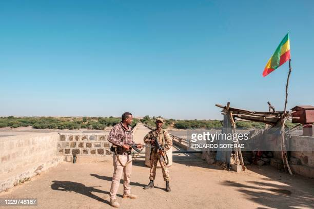 Member of the Amhara Special Forces with a member of the Amhara militia stand at the border crossing with Eritrea where an Imperial Ethiopian flag...
