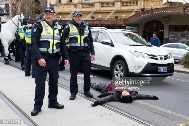 A member of the antiracism protest group lays on the middle of the road surrounded by police during a protest organised by the antiIslam True Blue...