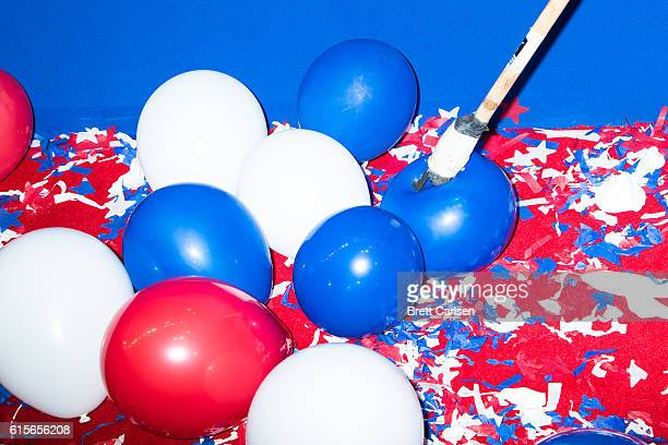 A member of the arena staff works to pop all of the balloons dropped from the ceiling after the Republican National Convention came to a close on...