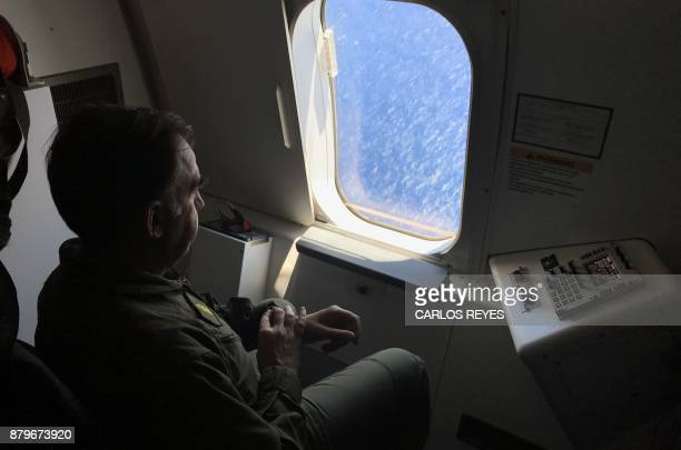 A member of the Argentine navy looks out the window of a P8A Poseidon aircraft of the US Navy Patrol and Reconnaissance Wing 11 as it assists the...