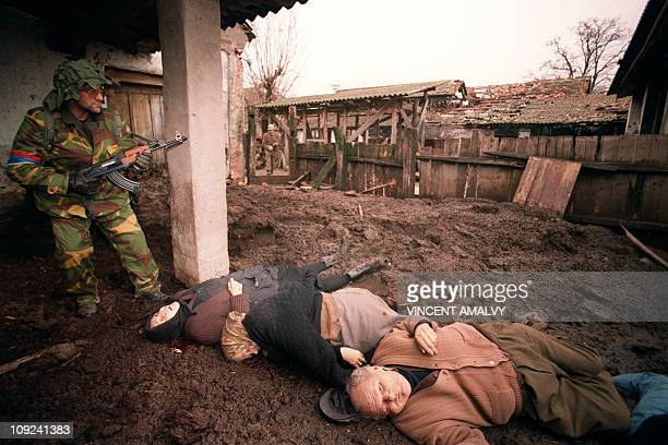 Member of the ''Arkan's Tigers'' Serb paramilitary group' stands over the bodies of three Croatian villagers whose throats were cut on November 24...