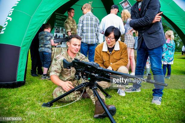A member of the Armed Forces demonstrates to a student how a GPMG operates during the event Stirling shows its support of the UK Armed Forces as part...