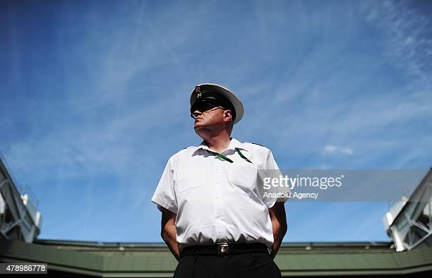 A member of the Armed Forces watches spectators on Centre Court during day one of the Wimbledon Lawn Tennis Championships at the All England Lawn...