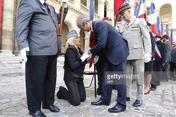 A member of the association 'Amazones' gathering Harkis relatives's Aline Carabetta kneels in front of French Junior Minister for Veterans' affairs...