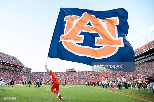 A member of the Auburn Tigers cheerleading squad waves the school flag after scoring during their game against the Arkansas State Red Wolves on...