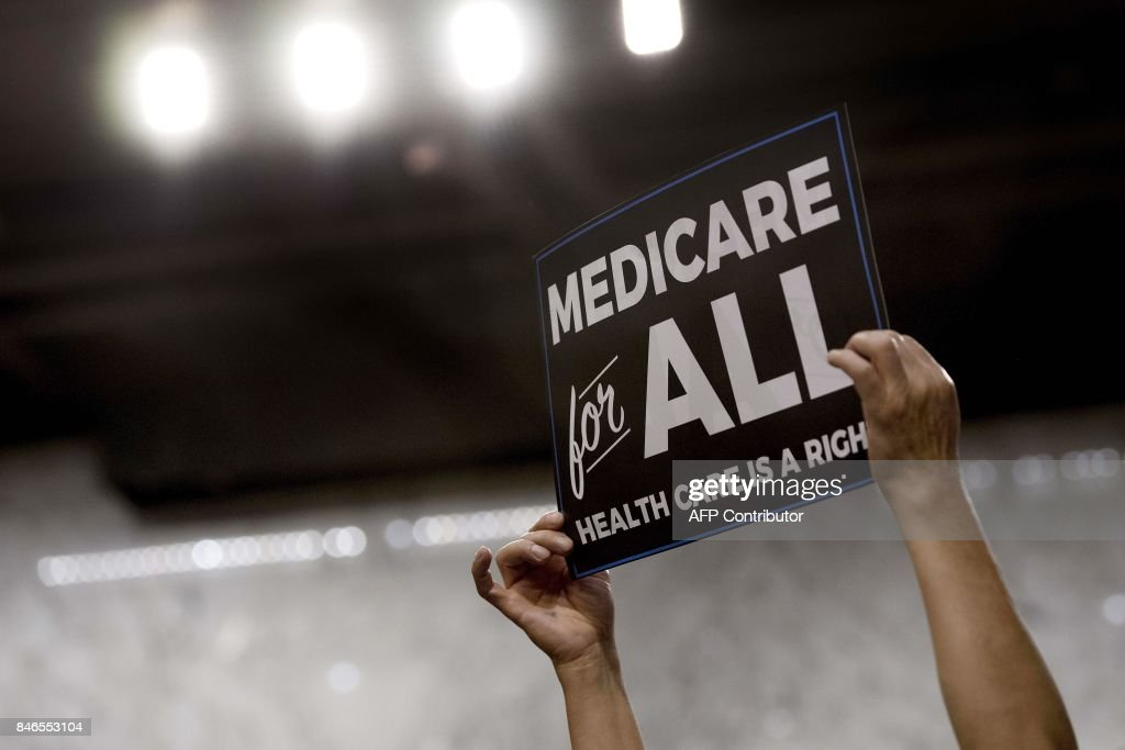 A member of the audience holds up a placard as US Senator Bernie Sanders, Independent from Vermont, discusses Medicare for All legislation on Capitol Hill in Washington, DC, on September 13, 2017. The former US presidential hopeful introduced a plan for government-sponsored universal health care, a notion long shunned in America that has newly gained traction among rising-star Democrats. /
