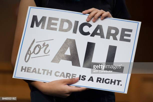 Member of the audience holds up a placard as US Senator Bernie Sanders, Independent from Vermont, discusses Medicare for All legislation on Capitol...