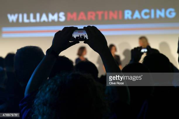 A member of the audience takes a picture during the Williams Martini Racing formula one car livery launch on March 6 2014 in London England