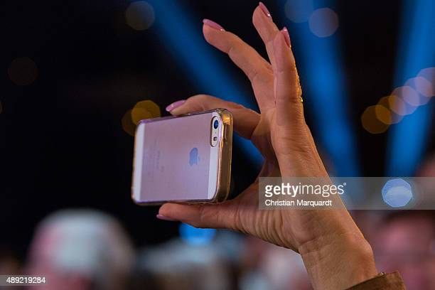 A member of the audience takes a picure by using a iphone wwwduring the television show 'Willkommen bei Carmen Nebel' at Velodrom on September 19...