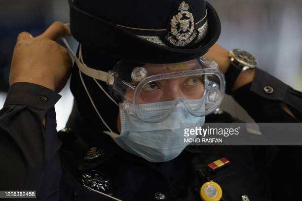 Member of the auxiliary police adjusts her goggles amid concerns over the spread of the COVID-19 coronavirus at the main entrance of the departure...