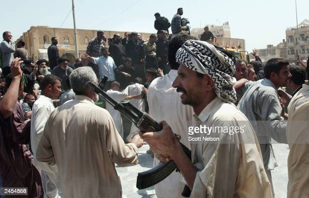 Member of the Badr Brigades, the private militia of assasinated Shiite cleric Mohammed Baqir al-Hakim brandishes an AK-47 outside the Imam Ali Shrine...