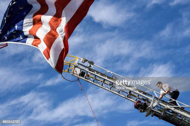A member of the Baltimore City Fire Department ascends a hook and ladder truck to adjust the flag which will fly over the cemetery as Detective Sean...