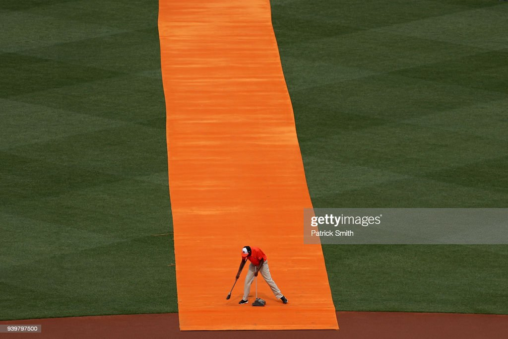 A member of the Baltimore Orioles grounds crew cleans an orange carpet before the Baltimore Orioles are introduced before they play against the Minnesota Twins in their Opening Day game at Oriole Park at Camden Yards on March 29, 2018 in Baltimore, Maryland.