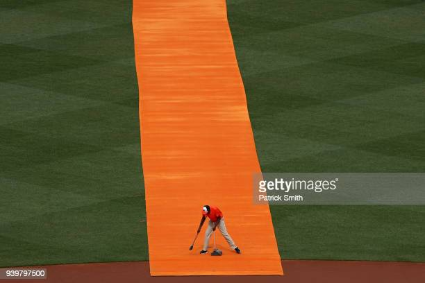 A member of the Baltimore Orioles grounds crew cleans an orange carpet before the Baltimore Orioles are introduced before they play against the...