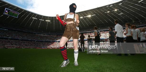 A member of the band Hidden Camera dances prior to the Franz Beckenbauer Cup match between Bayern Munich and Barcelona at the Allianz Arena on August...