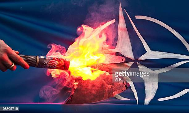 A member of the banned NationalBolshevik Party sets on fire a flag bearing the North Atlantic Treaty Organization logo during a protest on April 5...