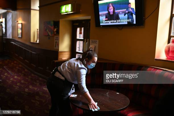 Member of the bar staff cleans a table in a Wetherspoons pub in Leigh, Greater Manchester, northwest England on October 22, 2020 ahead of new...