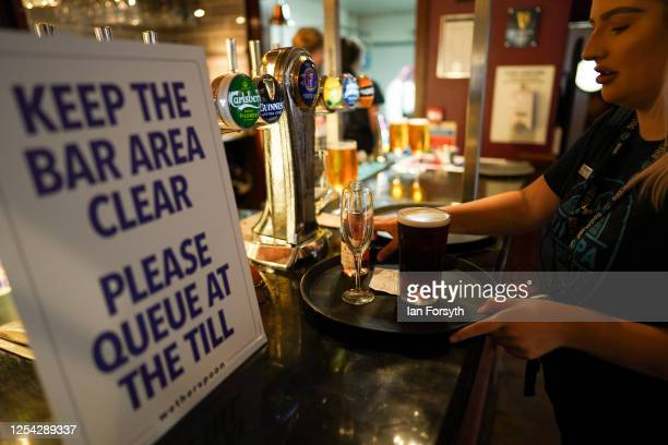 Member of the bar staff loads drinks onto a tray to deliver to customers on the first day of pubs reopening at the Job Bulman pub in Gosforth on July...