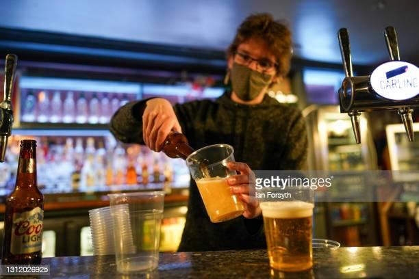 Member of the bar staff pours drinks in the Switch bar as it opens following the easing of lockdown measures on April 12, 2021 in Newcastle Upon...