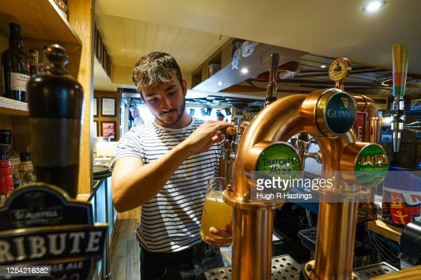 A member of the bar staff pulls a pint at the Chain Locker pub as it reopens for business on July 4 2020 in Falmouth Cornwall United Kingdom The UK...