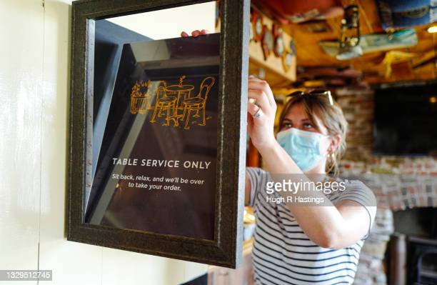 Member of the bar staff removes old Covid-19 signage inside the Chainlocker pub on July 19, 2021 in Falmouth, England. As of 12:01 on Monday, July...