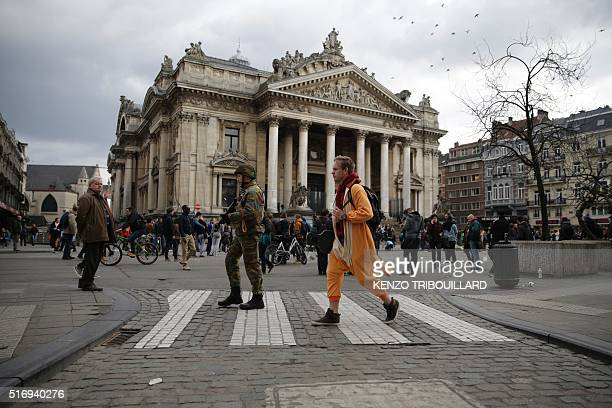 A member of the Belgian armed forces patrols following attacks in Brussels on March 22 2016 Airlines cancelled hundreds of flights and European...