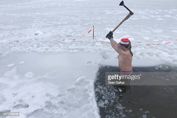 A member of the Berlin Seals swimming club prepares a hole in the ice prior to the club's traditional Christmas Day ice swim on December 25 2010 in...