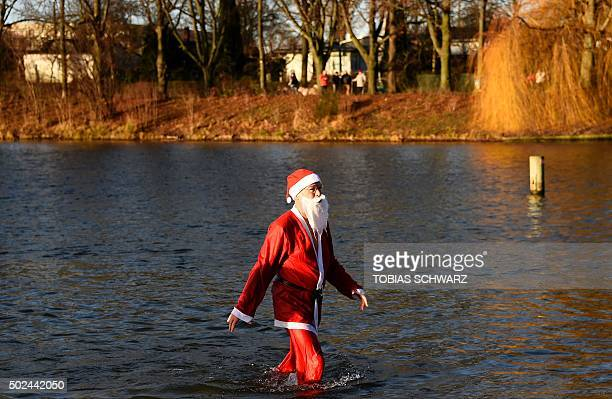 A member of the Berliner Seehunde swimming club is dressed as Father Christmas during their traditional Christmas swimming on December 25 2015 at the...