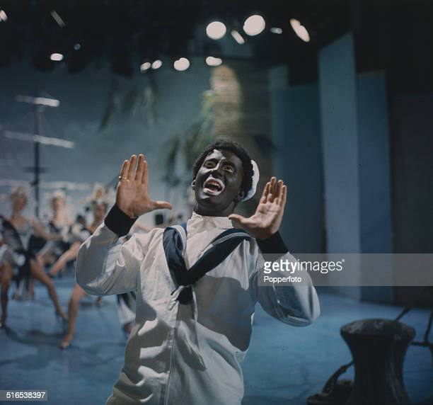 A member of The Black and White Minstrel Show wearing Blackface theatrical makeup performs on stage in 1964