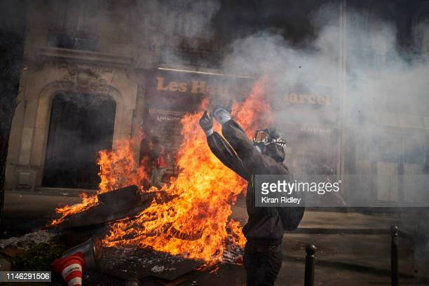 A member of the Black Block gestures towards police next to a burning barricade as demonstrations for International Labour Day turn violent with...