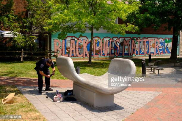 """Member of the Bloomington Police Department conducts a vandalism investigation at the site of the mural. The words, """"Black Lives Matter"""" painted over..."""