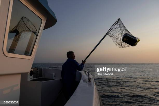 Member of the boat crew nets a spent fuel can, used by migrants to cross the English Channel on July 22, 2021 in Dover, England. On Monday, 430...
