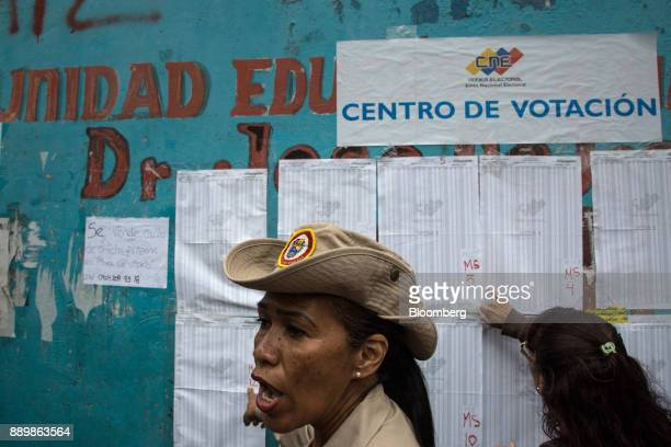 A member of the Bolivarian Militia gestures towards a registration list outside a polling station during a nationwide mayoral election in Caracas...