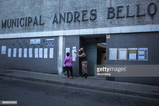A member of the Bolivarian Militia speaks with a voter outside a polling station during a nationwide mayoral election in Caracas Venezuela on Sunday...