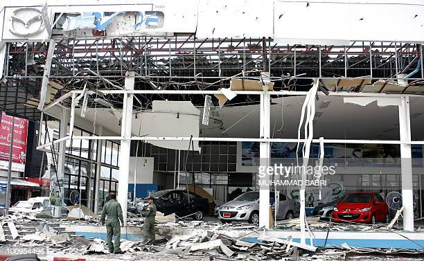 Member of the bomb squad inspect a damaged car showroom after a bomb exploded that was set allegedly by Muslim militants in Yala province on May 26...